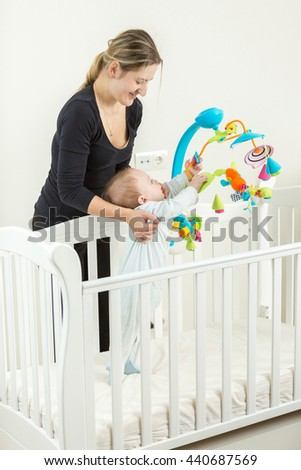 Happy young mother holding cute baby boy standing in white wooden cot - stock photo