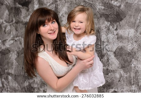 happy young mother holding her laughing little daughter on gray wall background - stock photo