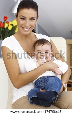 Happy young mother holding little boy in arms, both smiling. - stock photo