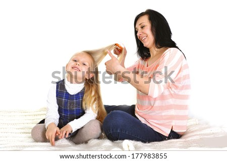 happy young mother holding remote and playful daughter watching television tv lying on bed together - stock photo