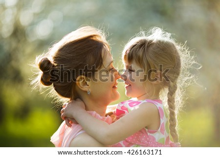 Happy young mother holds a baby daughter with pigtails - stock photo