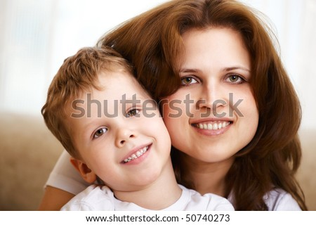 happy young mother hugging her little son indoor