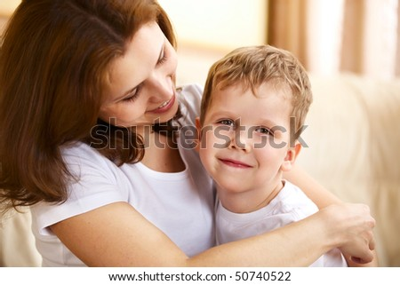 happy young mother hugging her little son indoor - stock photo