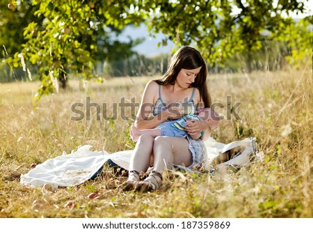 Happy young mother is feeding her baby boy in nature - stock photo