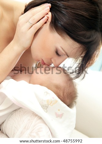 Happy young mother kissing a baby - stock photo