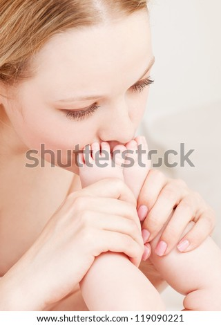 happy young mother kissing her four months old daughter's feet in bed at home - stock photo