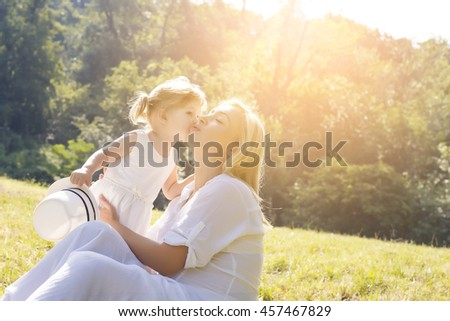 Happy young mother playing with daughter on sunny day in a meadow. Happy family concept - stock photo