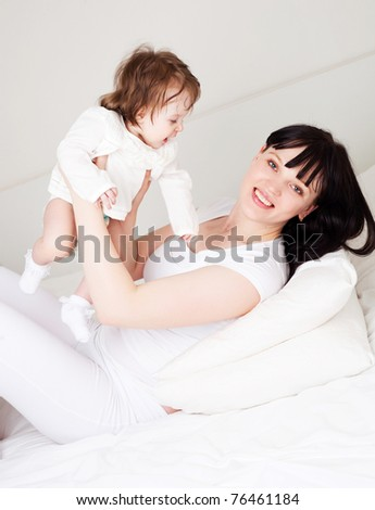 happy young mother playing with her baby on the bed at home (focus on the woman)