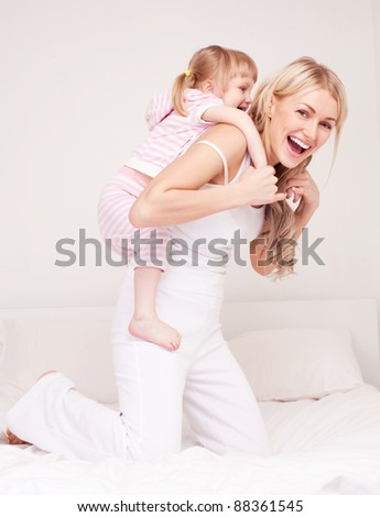 happy young mother playing with her daughter on the bed at home - stock photo
