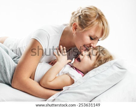 happy young mother playing with her daughter on the bed on white - stock photo