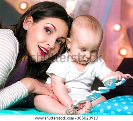 Happy young mother playing with little baby on white background