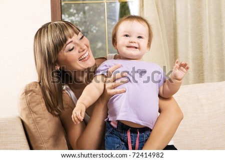 Happy young mother playing with little daughter at home - stock photo