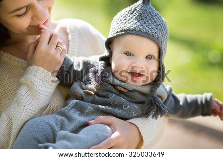 Happy young mother playing with little son in autumn park - stock photo