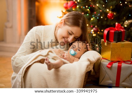Happy young mother posing with newborn son under Christmas tree - stock photo