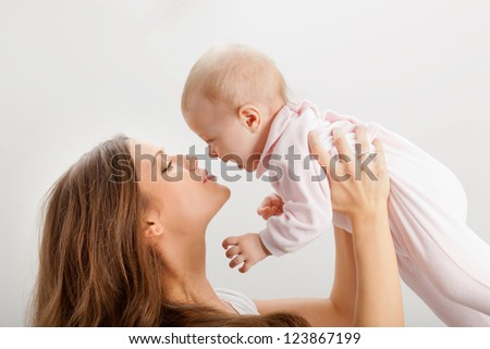 happy young mother rising her baby girl - stock photo