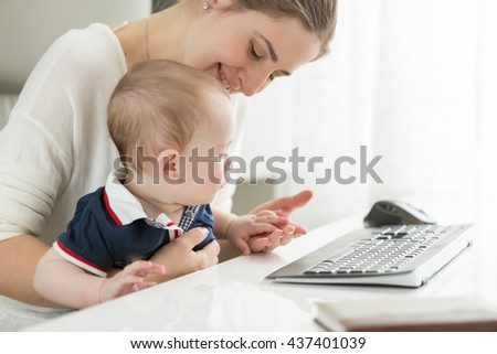 Happy young mother sitting at computer and holding her baby on lap - stock photo