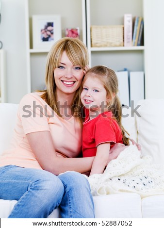Happy young  mother  sitting on the sofa and embracing her loving little daughter - indoors - stock photo