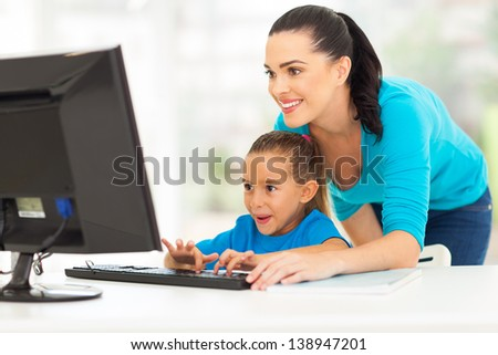 happy young mother teaching daughter computer at home - stock photo