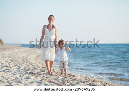 Happy young mother walking along the beach with her little son waving to camera - stock photo