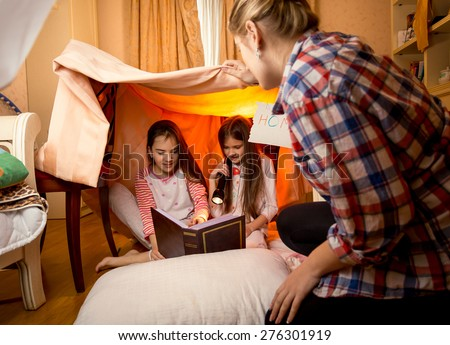 Happy young mother watching at two daughters reading book on floor at bedroom - stock photo
