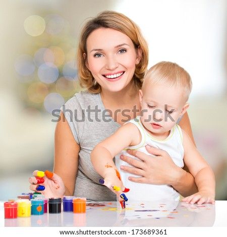 Happy young mother with a baby paint by hands - at home.