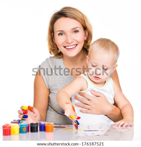 Happy young mother with a baby paint by hands - isolated on white.