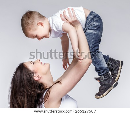 happy young mother with a child on light grey background - stock photo
