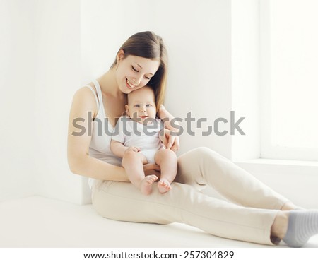 Happy young mother with baby at home in white room near window - stock photo