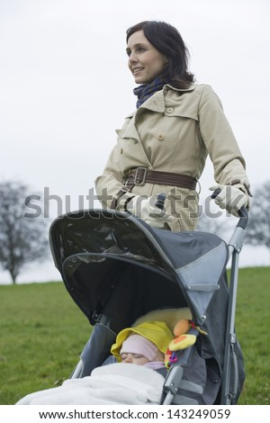 Happy young mother with baby in stroller at park