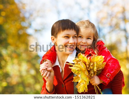 Happy young mother with daughter in autumn park