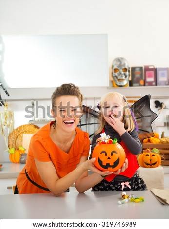 Happy young mother with daughter in bat costume eating colorfull halloween candy in decorated kitchen.  Halloween Candy is so good. Traditional autumn holiday - stock photo