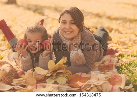 Happy young mother with daughter on autumn picnic - stock photo