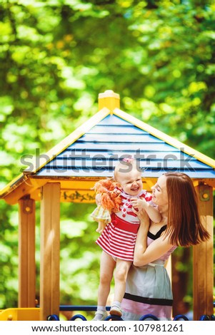 Happy young mother with daughter playing together in green summer park outdoors