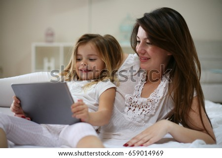 Happy young mother with daughter using digital tablet on bed at home.