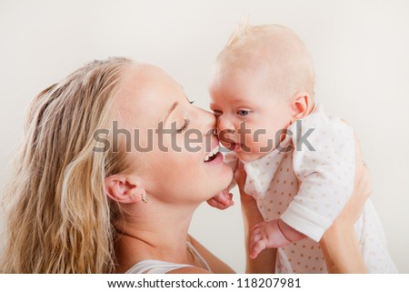 Happy young mother with her baby on white background. Happy family with newborn.