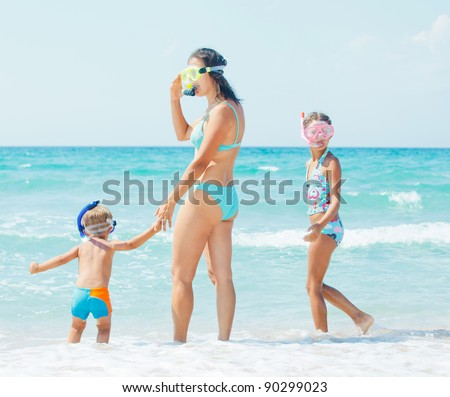 Happy young mother with her child with snorkeling equipment on sandy tropical beach - stock photo