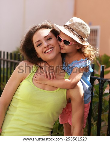 Happy young mother with her cute kid girl in sun glasses outdoors. Beautiful family