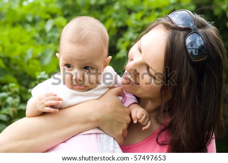 Happy young mother with her daughter in the summer park - stock photo