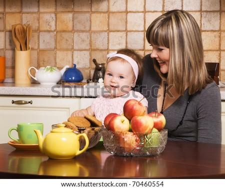 Happy young mother with her little daughter at kitchen - stock photo