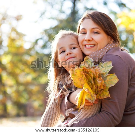 Happy young mother with her little daughter in autumn park - stock photo