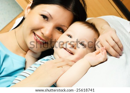 happy young mother with her ten months old baby on the bed - stock photo