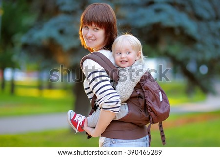 Happy young mother with her toddler child in a baby carrier - stock photo
