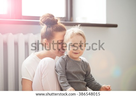 Happy young mother with little son on bedroom home background - stock photo