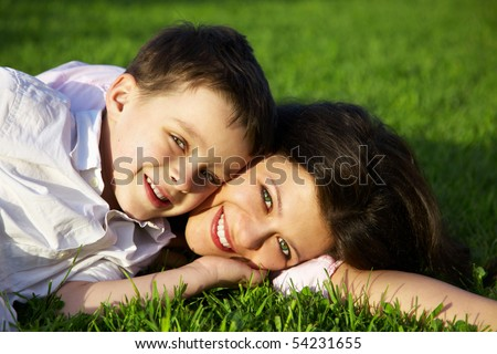happy young mother with son lying on grass - stock photo