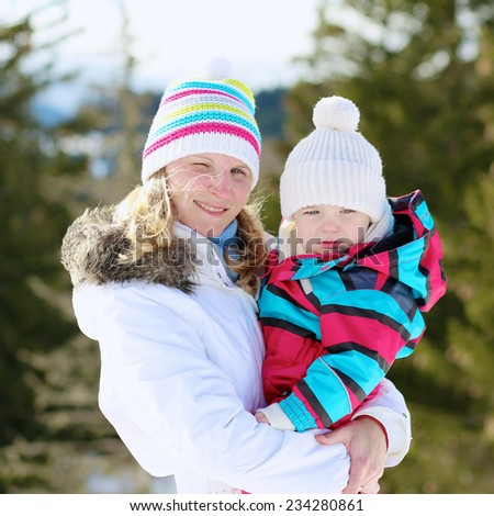 Happy young mother with toddler daughter in colorful snowsuit enjoying apres-ski during vacation in snowy alpine village - stock photo