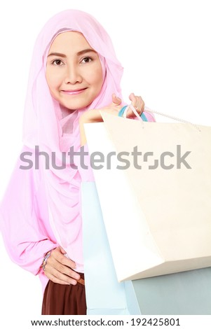 happy young muslim woman with shopping bag isolated on white background - stock photo