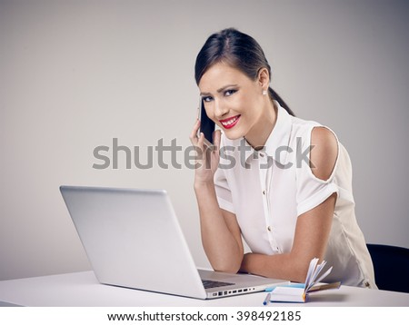 Happy young office girl smiling during phone conversation