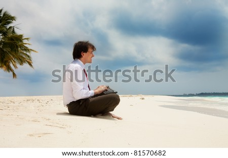 Happy young office worker sitting on the sand near the sea with keyboard - stock photo