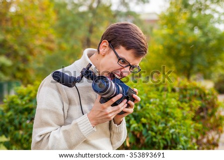 Happy young operator with a video camera in the park playing the fool - stock photo