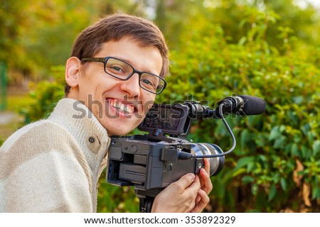 Happy young operator with a video camera shoots video in the park  - stock photo